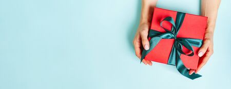 Female hands is holding present red box with green bow on pastel green background with copy space. Flat lay style. Christmas festive spirit. Mockup for New Year. Banner. Banco de Imagens