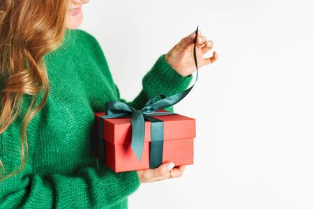 Female in woolen sweater holding present red gift box with bow. Christmas festive spirit. Mockup for New Year. Wide banner.