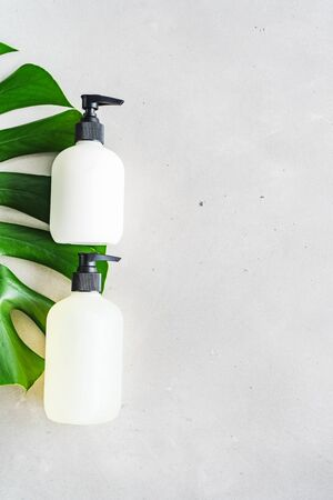 Cosmetic set of two blank label bottles for mock-up packaging of skincare product cream, shampoo, conditioner on grey background with green leaves. Natural beauty product concept.