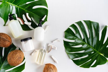 Set bottles of organic body care cosmetic products on monstera leaves with pieces of coconut over white textile background. SPA branding mock-up, place your design of natural skincare concept. Banque d'images