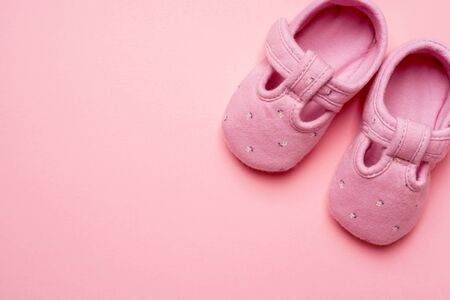Baby textile Slippers for girl on pink background with copy space.