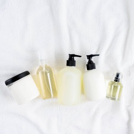 Set of Bottles with organic body care cosmetic products shampoo, conditioner, body oil, fragrance, soap, cream, lotion on white fluffy towels on a light background. Concept of SPA branding mock-up.