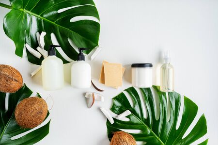 Set bottles of organic body care cosmetic products on monstera leaves with pieces of coconut over white textile background. SPA branding mock-up, place your design of natural skincare concept. Stock Photo