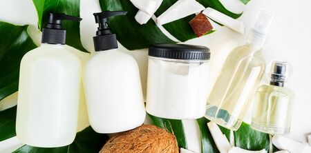 Set bottles of organic body care cosmetic products shampoo, conditioner, body oil, fragrance, soap on monstera leaves with pieces of coconut over white textile background. SPA branding mock-up. Stock Photo