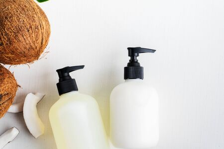 Close up of two bottles for organic body care cosmetic products with coconuts over white textile background. SPA branding mock-up, place your design of natural skincare concept.