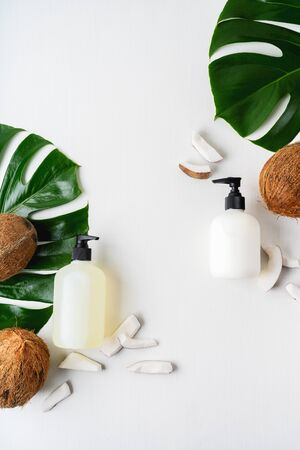 Close up of two bottles for organic body care cosmetic products on green monstera leaves, coconuts over white textile background. SPA branding mock-up, place your design of natural skincare concept.
