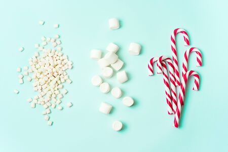 Christmas layout with candy cane, and different sizes marshmallows on a turquoise background. Ingredients for Christmas mood.