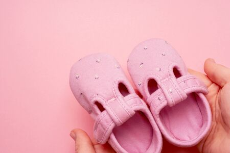 Girls Baby textile Slippers in a hands female on pink background with copy space.