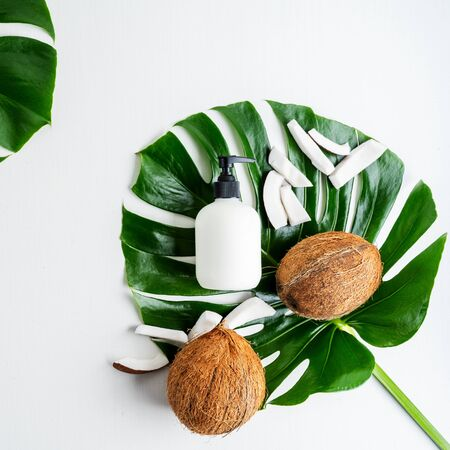 Bottle with cream organic body care cosmetic products on monstera leaves with pieces of coconut over white textile background. SPA branding mock-up.