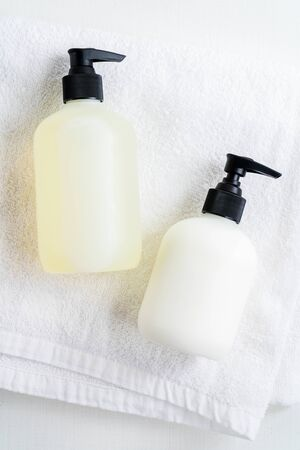 Set of Bottles with organic body care cosmetic products on white fluffy towels on a light background. Concept of SPA branding mock-up. Фото со стока