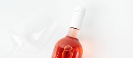 Bottle of rose wine for label layout with glass of wine on white background.