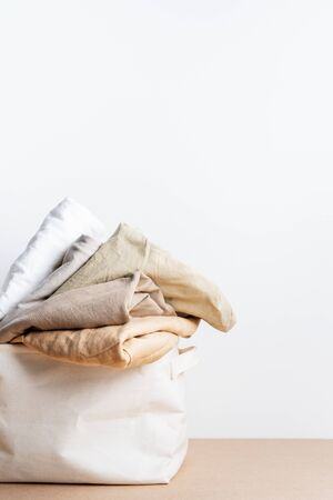 Clean clothes in the basket of laundry. Space for text. Bio-organic product layout. Standard-Bild