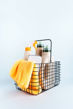 ?lose-up of bottles of cleaning products and microfiber cloth, cleaning sponge in basket on blue white background overview with space for text. Front view. Cleaning tools, cleanliness and cleaning layout.