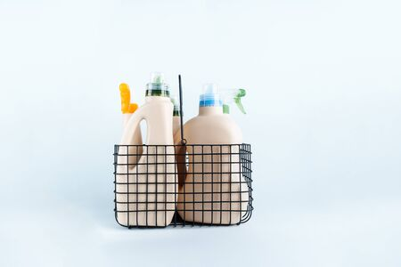 Ð¡lose-up of bottles of cleaning products and microfiber cloth, cleaning sponge in basket on blue white background overview with space for text. Front view. Cleaning tools, cleanliness and cleaning