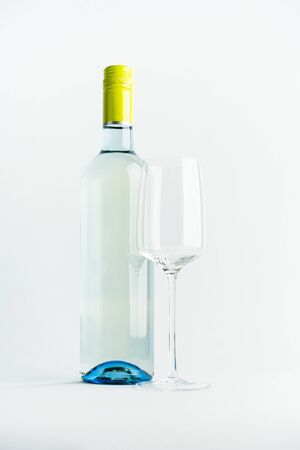 A bottle of white wine for the label layout with a glass of wine on a light background. alcoholic beverage. branding Standard-Bild - 130061626