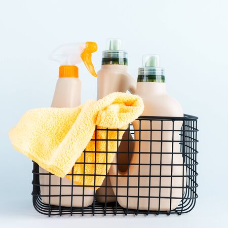Ð¡lose-up of bottles of cleaning products and microfiber cloth, cleaning sponge in basket on blue white background overview with space for text. Front view. Cleaning tools, cleanliness and cleaning layout. Standard-Bild
