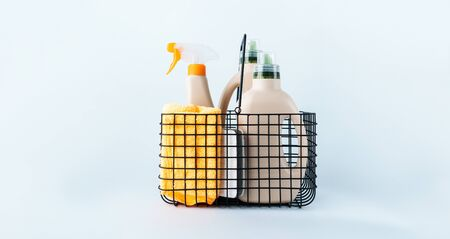 Ð¡lose-up of bottles of cleaning products and microfiber cloth, cleaning sponge in basket on blue white background overview with space for text. Front view. Cleaning tools, cleanliness and cleaning layout.