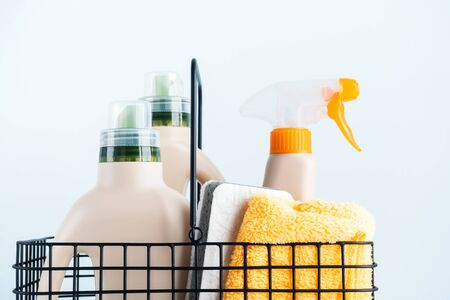 Сlose-up of bottles of cleaning products and microfiber cloth, cleaning sponge in basket on blue white background overview with space for text. Front view. Cleaning tools, cleanliness and cleaning la