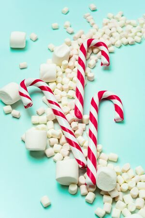 Christmas or New year holiday layout with candy canes and marshmallows on a turquoise background with copy space. Greeting card with Christmas props. Standard-Bild - 132620059