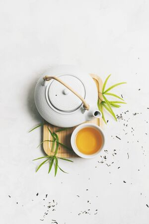 Asian tea concept with Tea set on bamboo mat surrounded with dry green tea on white background with copy space. Brewing and Drinking tea. Standard-Bild