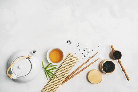 Asian food concept with Tea set, chopsticks, bamboo mat, on white background for your own design. Standard-Bild