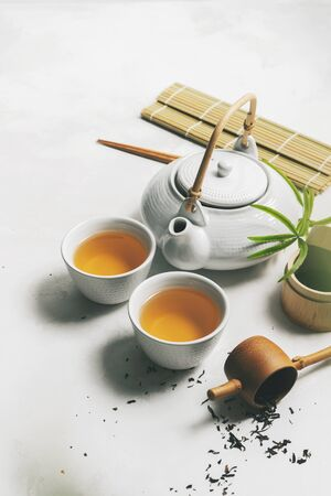 Asian tea concept, two white cups of tea, teapot, Tea set, chopsticks, bamboo mat surrounded with dry green tea on white background with space for text. Brewing and Drinking tea.