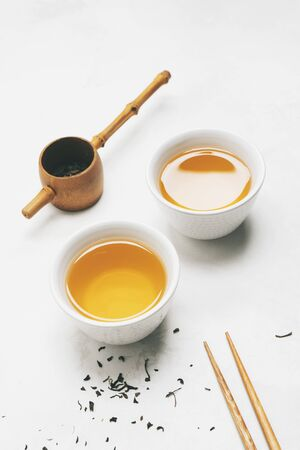 Asian tea concept, two white cups of tea, teapot, Tea set, chopsticks, bamboo mat surrounded with dry green tea on white background with copy space. Brewing and Drinking tea. Standard-Bild