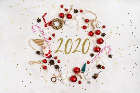 Merry Christmas and New Year 2020 greeting card in a round frame, banner.  Happy Holidays Creative layout. Christmas props tree toys on white background top view. Winter holiday xmas theme. Standard-Bild