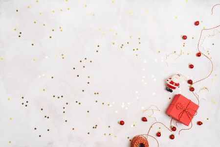 Christmas or New Year holiday winter layout with red gift boxes, rope, vintage decorations props over on white background with confetti and space for text. Wrapping presents.