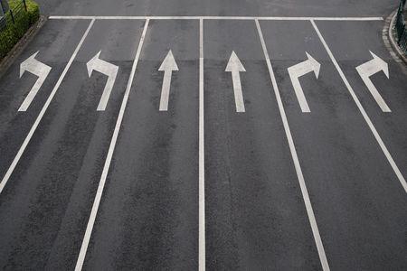 autopista: Signos de flecha como marcas de la carretera en una calle con seis carriles