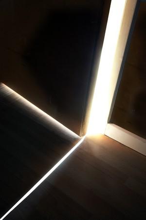 shining through: Luce del sole che splende attraverso un piccolo divario tra la porta un muro Archivio Fotografico