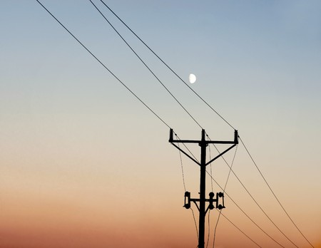 power cable: Silhouette of electricity pole against evening sky Stock Photo