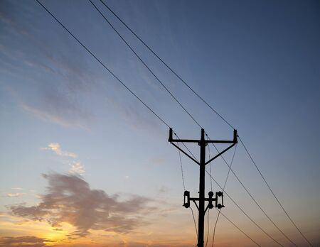 Silhouette of electricity pole against evening sky photo
