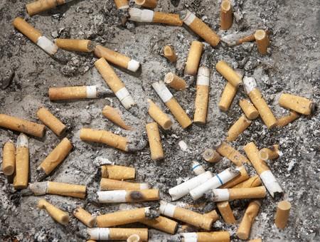 Cigarette buts in a public ashtray