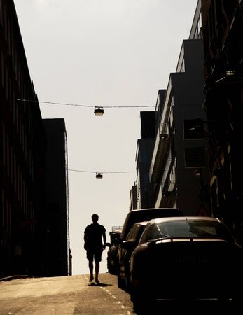 Silhouette of a young man walking along a street in evening light photo