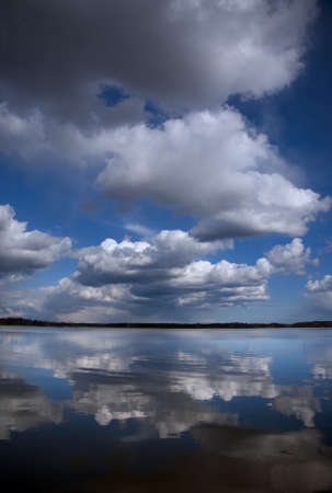 Fluffy clouds in blue sky reflected in water