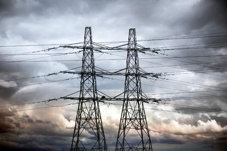 redes electricas: Dos torres de electricidad contra el cielo de la noche de Rosa y gris moody