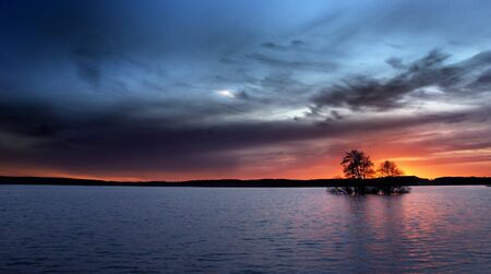 A small island with trees in sunset Stock Photo - 8175306