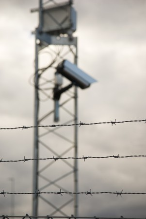 Defocused surveillance camera behind barbed wire. Focus on the wire photo