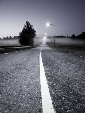 Rural asphalt road in a foggy evening Stock Photo - 8175525