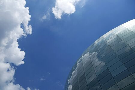 globe grid: Spherical glass facade reflecting the blue sky and white clouds Stock Photo