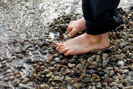 stone cold: Two small feet on pebbles on the beach