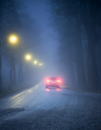 Car driving in a dark avenue in thick fog Stock Photo
