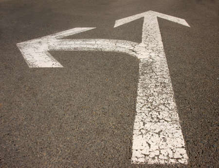 White arrow on the road pointing in two directions Stock Photo - 8305219