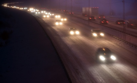 Heavy traffic on the highway in a hevy snowstorm at night Stock Photo