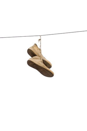 A pair of old sneakers hanging from a cable, isolated on white photo