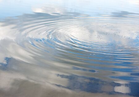 Circles and bubbles on a blue water surface, with reflection of white clouds photo