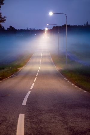 Small rural road in a foggy evening, with street lights