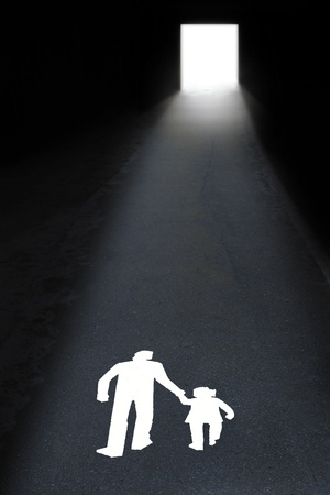 towards: A man and a child walking towards the light Stock Photo