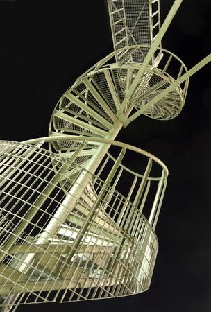 under fire: Escalera de caracol contra el cielo de la noche negra.